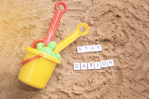 Staycation bucket and shovel on sand